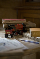 Antique red toy train amongst books and letters