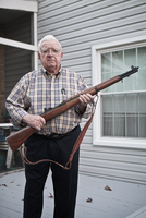 Retired US Navy commander holding a WWII rifle. U.S.A