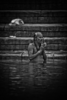 Older male Hindu devotee prays in the holy water of the River Ganges. Varanasi, India