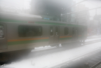 Foggy image of train in snow