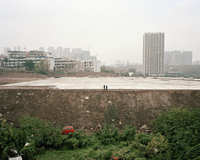 Two people wandering in a partly demolished construction site. Chongqing, China