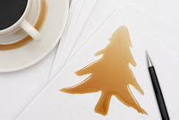 Christmas tree shaped coffee splash on pile of documents with cup of coffee