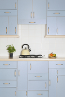 Kitchen interior with many blue cupboards and drawers and a kettle on the stove