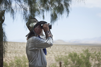 Cowboy with binoculars looking for cattle. Mojave desert, California, U.S.A