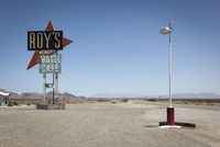 Sign for Roys Motel and cafe with large red arrow and lamppost on roadside. National Trails Hwy, Amboy, California, U.S.A
