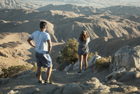Young tourist couple looking at Coachella Valley landscape and taking photo on camera phone at Keys View. Joshua Tree National P