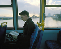Man reads a book on a bus crossing the Thames in London near Vauxhall, London, United Kingdom
