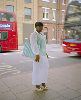 Smartly dressed woman waits for the bus in Vauxhall South London, United Kingdom