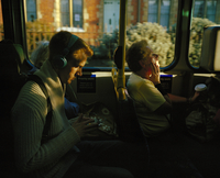 Man sits on the bus reading his phone and listening to music. London, United Kingdom