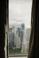 View through curtains in a hotel room of skyscrapers. Hong Kong, China