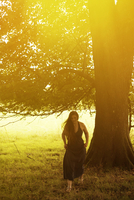 Woman wearing summer dress with sun flare and tree