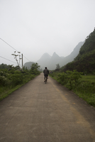 Cyclist cycles down a quiet country road amongst the Karst limestone hills and mountains. Yangshuo, China