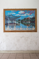 Idyllic and serene picture of a Chinese landscape on a poster pinned up against a dirty white wall in a corridor. China