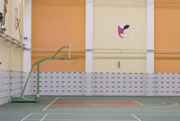 Chinese high school sports hall with a basketball hoop and dancing figure on wall. Shanghai, China
