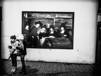 Two girls in at night texting in front of a Dutch old master painting. Amsterdam, Netherlands