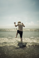 Rear view of boy jumping in sea