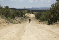 Cyclist on mountain bike cycling down lonesome unpaved road through spacious wide open countryside. New Mexico, U.S.A