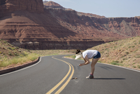 Woman wearing sun hat looking and photographing roadkill. Marble Canyon, Arizona, U.S.A