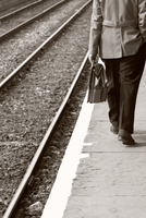 Businessman walking away holding a leather briefcase next to railway