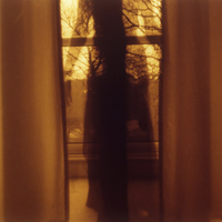 Translucent girl wearing long dress standing between plain curtains, girl and window merge to form crucifix, trees through windo