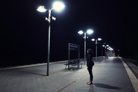 Woman waiting at train station at night on an empty platform lit by lamp posts