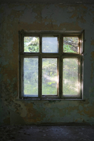 Old window with yellow paint peeling off the wall