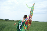 Rear view of a boy with a kite in his hand