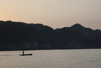 Silhouette of a fisherman standing on a small boat at dawn. Vietnam