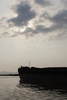 Silhouette of a long barge boat. Vietnam