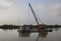 Barge and crane over the sea in the channel of Haiphong, Vietnam