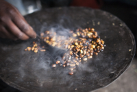 Close-up of a woman roasting coffee on a piece of metal. Ethiopia