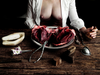 Woman sitting at table with raw meat