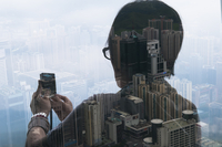 Double exposure of a woman at a window taking a photo with phone of a cityscape