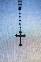 Crucifix hanging on window screen