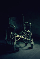Old and broken wheelchair in a dark room