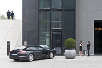 Office workers outside modern office building with a car parked outside. Dusseldorf, Germany