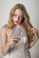 Young woman with long hair and wearing a gown using her cell phone