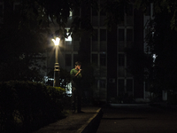 Man lights a cigarette under a lamppost at night, Pune, India