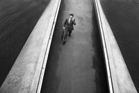 Man talking on mobile phone crossing a bridge. Geneva, Switzerland