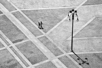 Aerial view of couple walking across square. Piazza del Duomo. Milan, Italy
