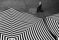 Businessman walking past large stripped parasols. Geneva, Switzerland
