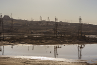 Oil fields reflected in pool of water. Azerbaijan