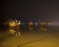 Three traditional boats moored at night. Muscat, Oman