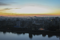 Cityscape at dusk reflection in the Taedong river. Pyongyang, North Korea