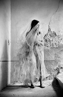 Nude woman wrapped in a veil standing in an abandoned building. Italy