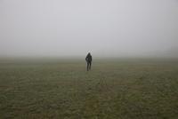 Rear view of man running in misty field