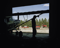 Silhouette of man leaning against wing strut of a small aeroplane inside a barn. Idalou, Texas, U.S.A