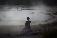 Rear view of woman sitting looking at geyser. Italy