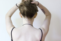 Rear view of young woman holding up hair.  England, United Kingdom
