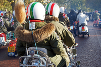 People wearing Italian flag helmets and parkas riding motor scooter at rally. Regent's Park, London, England, United Kingdom